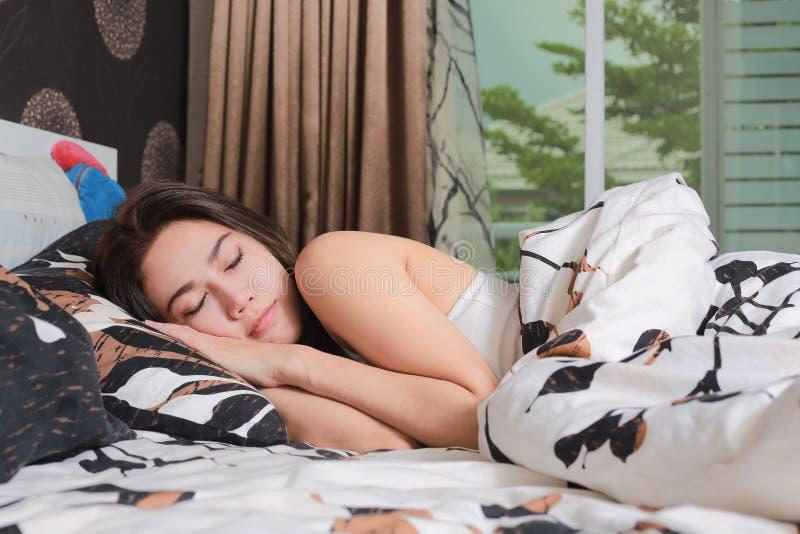 Giovane bella donna asiatica che dorme nel suo letto fotografia stock