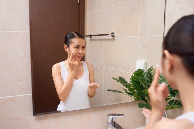 Giovane bella donna asiatica che lava il suo fronte con le mani dal sapone fotografie stock