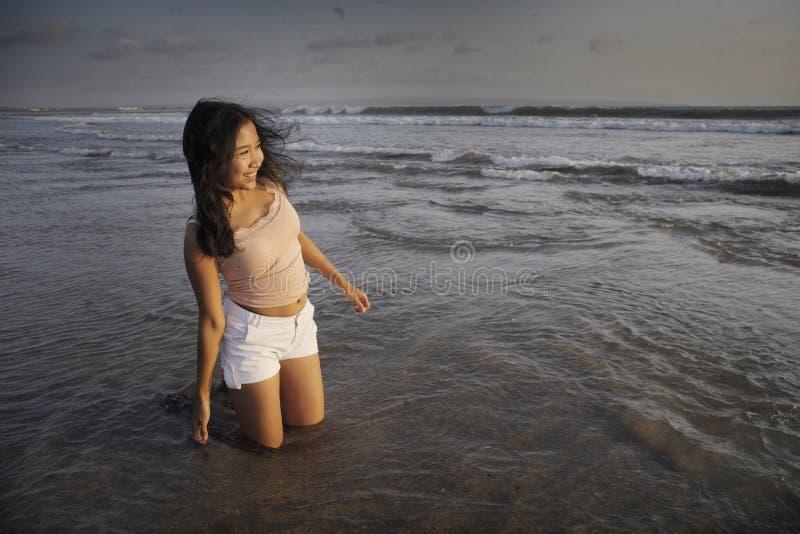 Giovane bella donna asiatica che sorride divertiresi libero e felice alla spiaggia di tramonto nell'isola di Bali dell'Indonesia  immagini stock