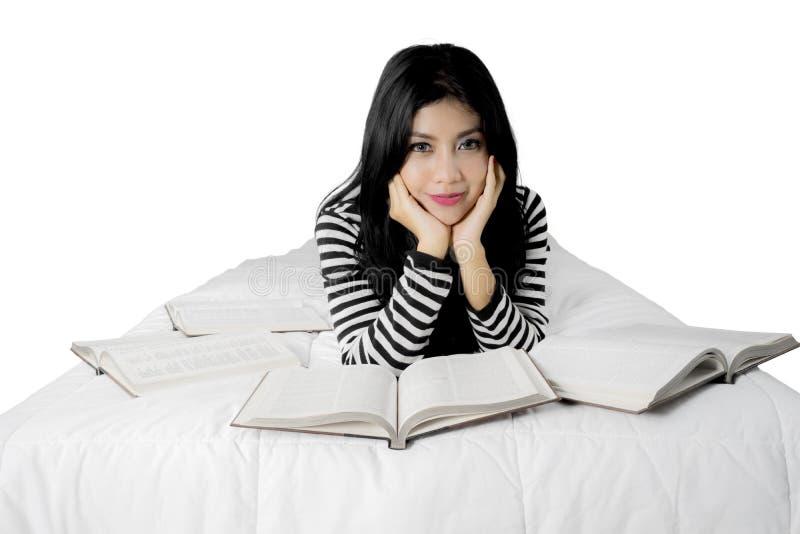 Giovane bella donna asiatica con il libro a letto immagine stock