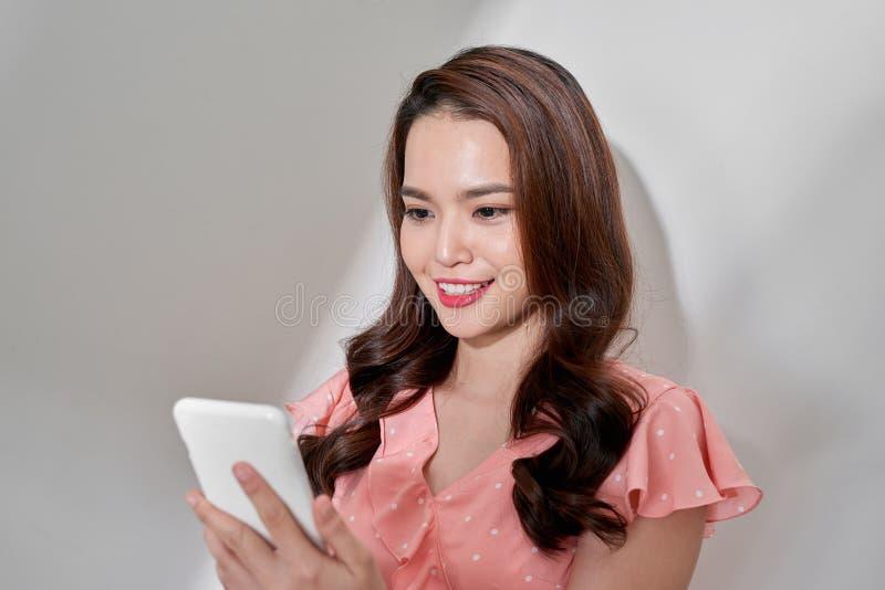 Giovane bella donna asiatica sicura che per mezzo dello smartphone fotografia stock libera da diritti