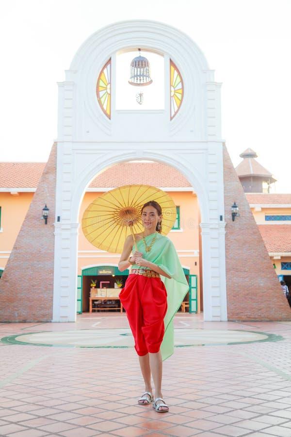 Giovane bella donna asiatica tailandese in costume tailandese tradizionale d'annata con l'ombrello nell'attesa all'ospite benvenu fotografia stock libera da diritti