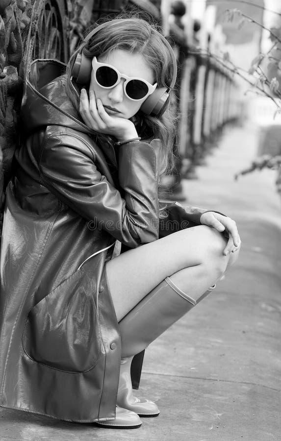 Giovane bella donna in attrezzatura luminosa che gode della musica a casa fotografia stock