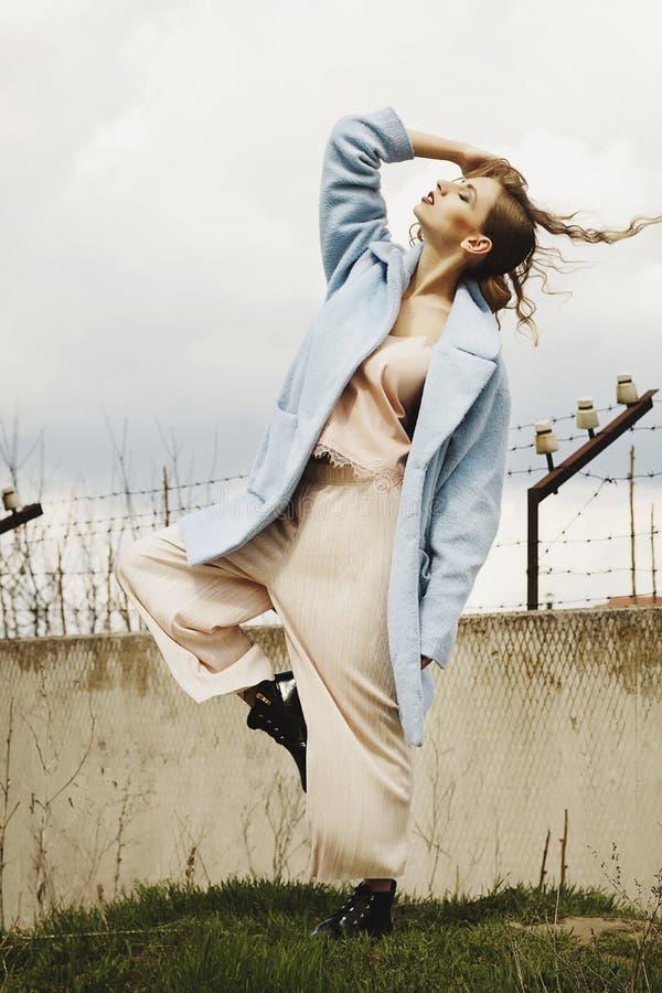 Giovane bella donna bionda che posa in cappotto blu all'aperto fotografia stock
