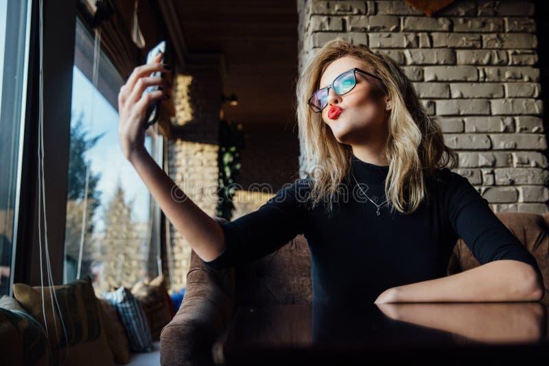 Giovane bella donna bionda che prende un selfie in caffetteria Pantaloni a vita bassa, labbra rosse, vetri immagini stock
