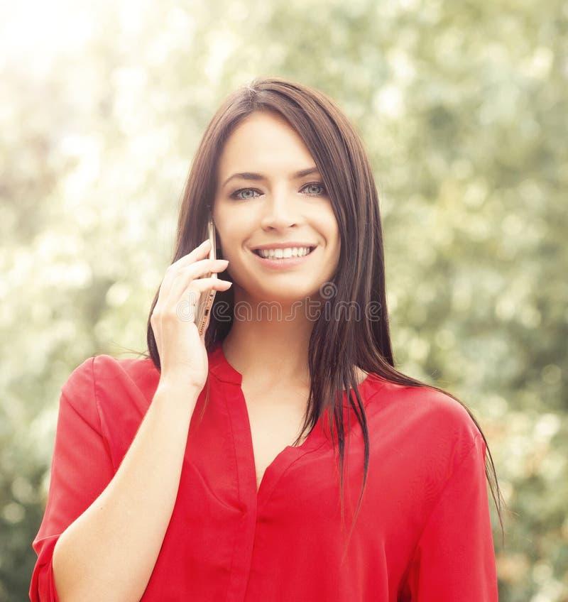 Giovane bella donna in blusa rossa fuori nel parco con una n immagine stock libera da diritti