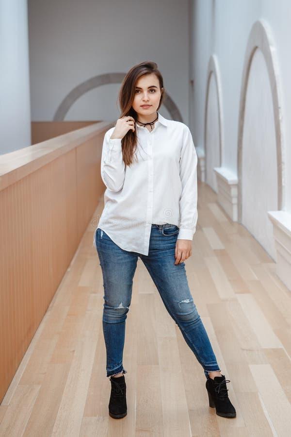 Giovane bella donna castana caucasica della ragazza con capelli scuri lunghi in camicia e blue jeans bianche immagini stock