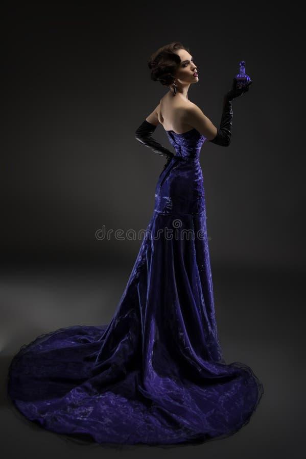 Giovane bella donna castana che posa con la bottiglia di profumo immagini stock