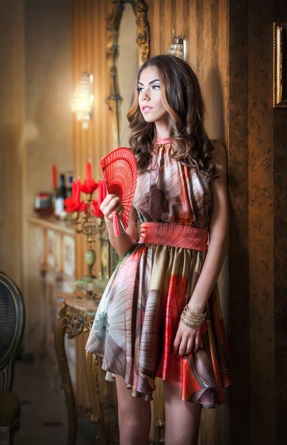 Giovane bella donna castana in vestito multicolore elegante che sta vicino ad un grande specchio della parete Signora romantica s fotografie stock libere da diritti