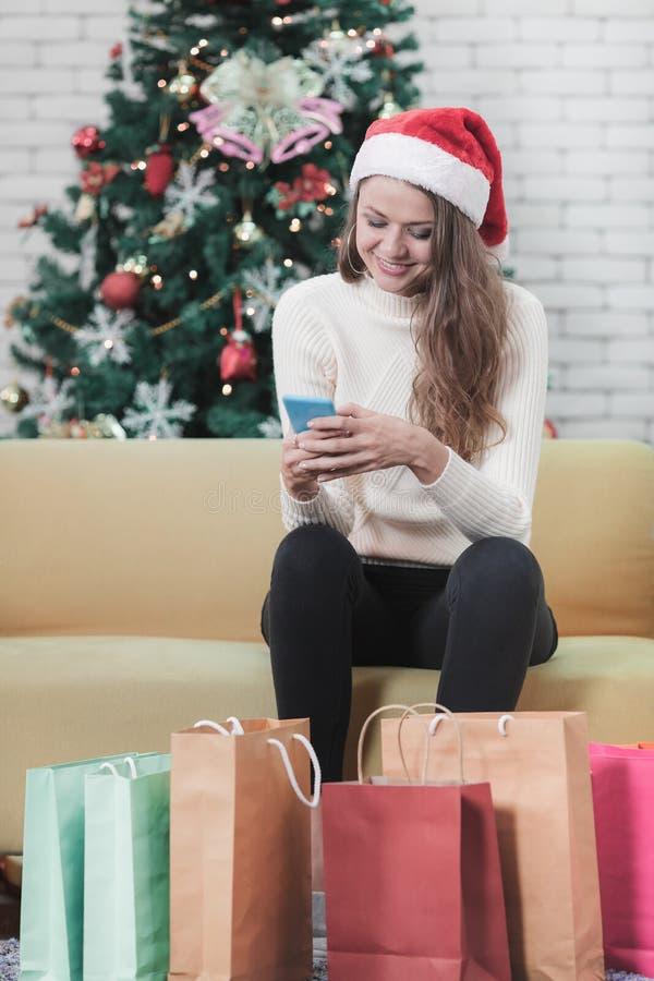 Giovane bella donna caucasica in cappello rosso che si siede sul sofà nel franco fotografia stock libera da diritti