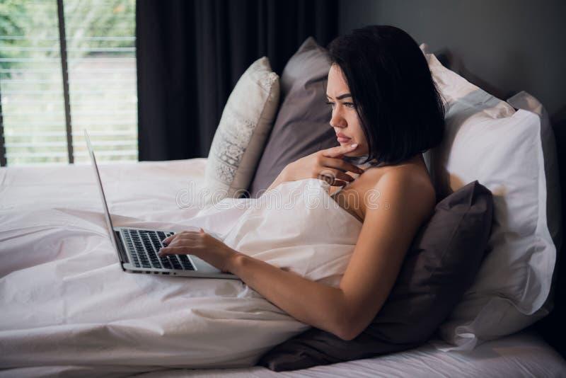 Giovane bella donna caucasica che mette su letto e che per mezzo del computer portatile per lavorare dopo che svegli e pensando a fotografia stock libera da diritti