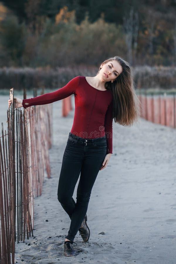 Giovane bella donna caucasica sola triste pensierosa con capelli lunghi sudici il giorno ventoso all'aperto sulla spiaggia della  fotografie stock libere da diritti