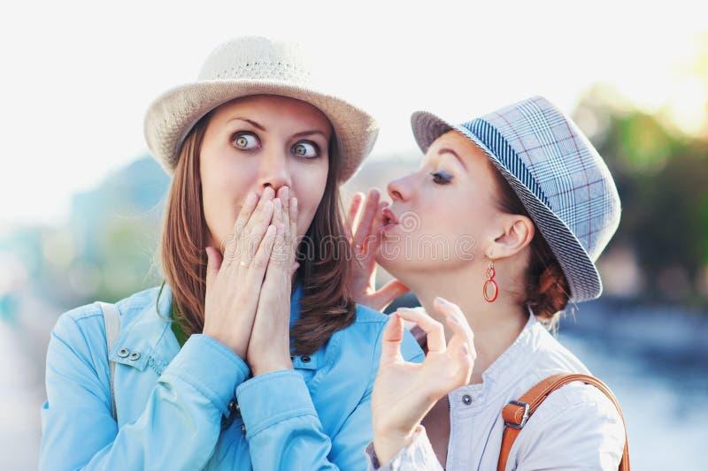 Giovane bella donna che dice segreto al suo amico fotografia stock