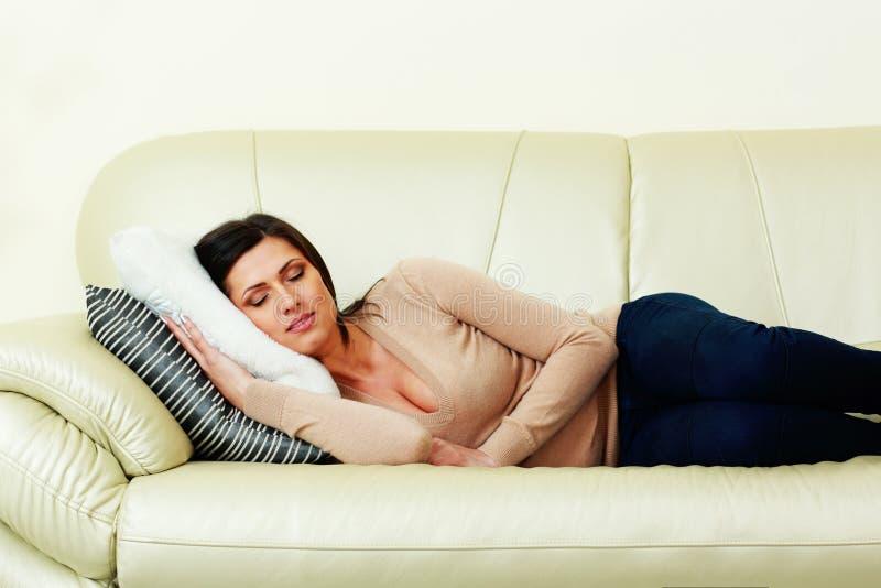 Giovane bella donna che dorme sul sofà fotografia stock libera da diritti