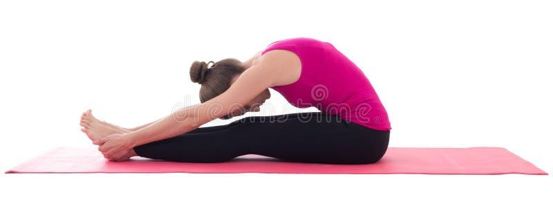 Giovane bella donna che fa allungando esercizio sull'isolante della stuoia di yoga immagini stock