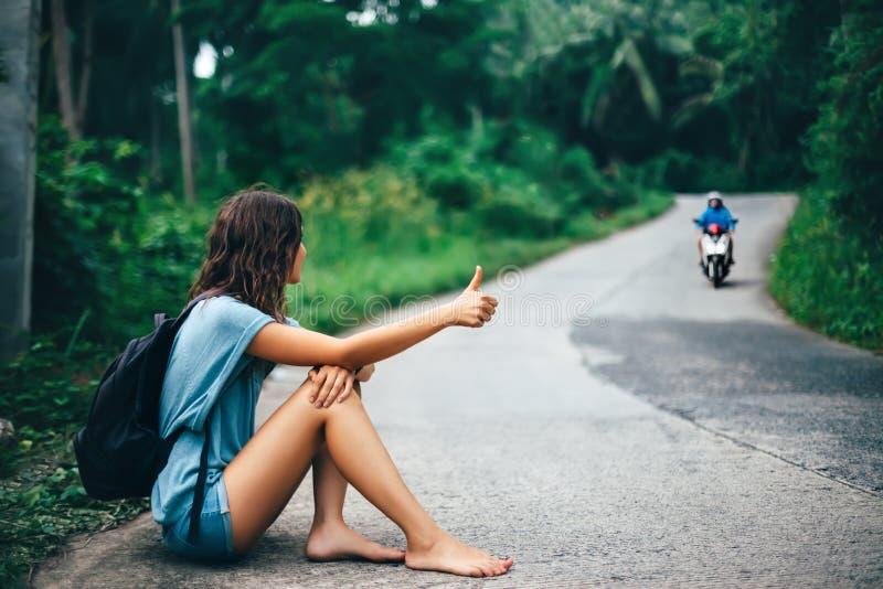 Giovane bella donna che fa auto-stop seduta sulla strada immagine stock