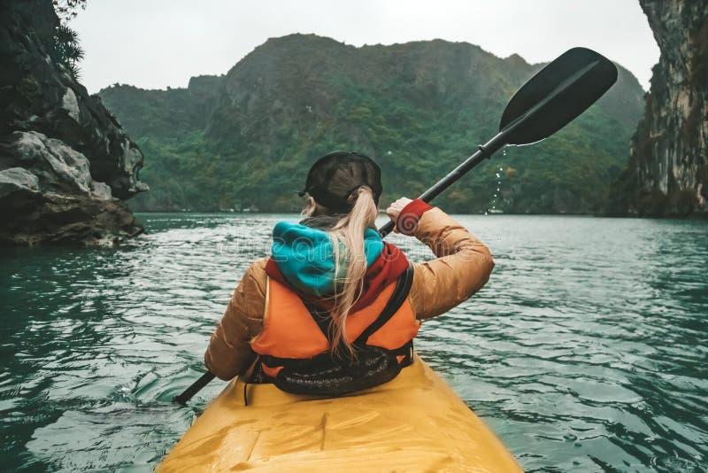 Giovane bella donna che galleggia su un kajak fra le rocce che attaccano dal mare La ragazza che rema i remi sui precedenti di fotografie stock libere da diritti