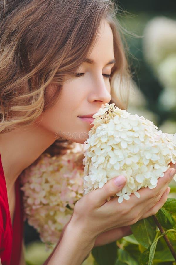 Giovane bella donna che gode dell'odore del fiore di fioritura un giorno soleggiato fotografia stock