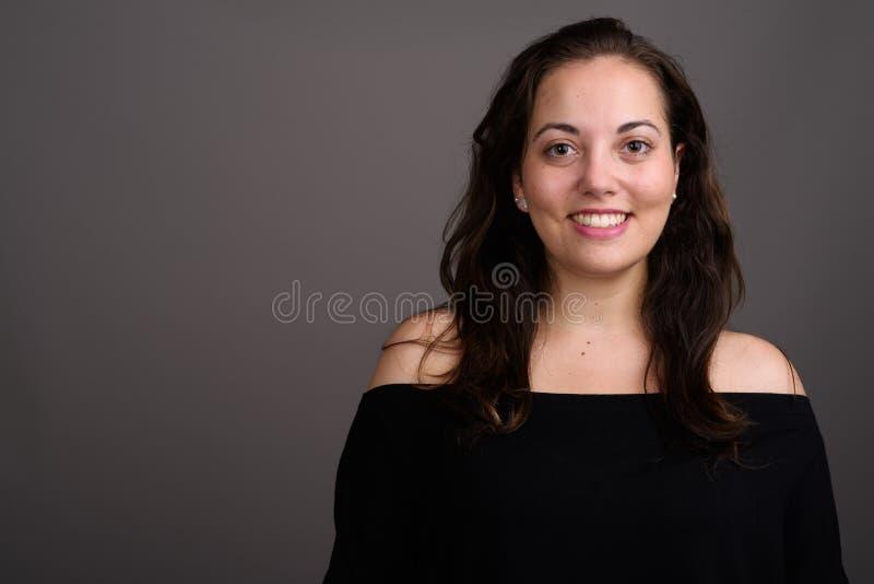 Giovane bella donna che indossa la cima nera della fuori spalla contro il gra fotografia stock