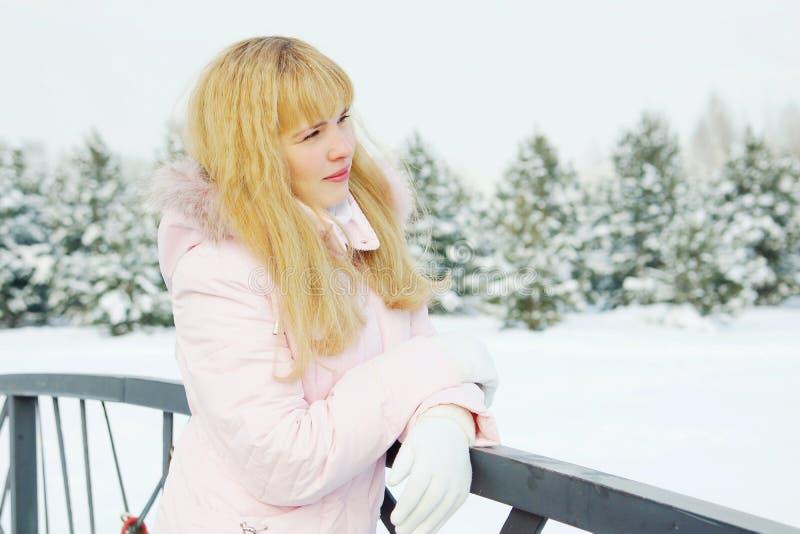 Giovane bella donna che indossa la natura piena d'ammirazione del rivestimento rosa nell'inverno fotografie stock libere da diritti