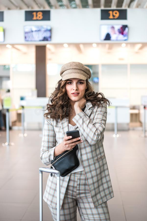 Giovane bella donna che legge i messaggi di telefono nella sala di attesa dell'aeroporto fotografia stock libera da diritti