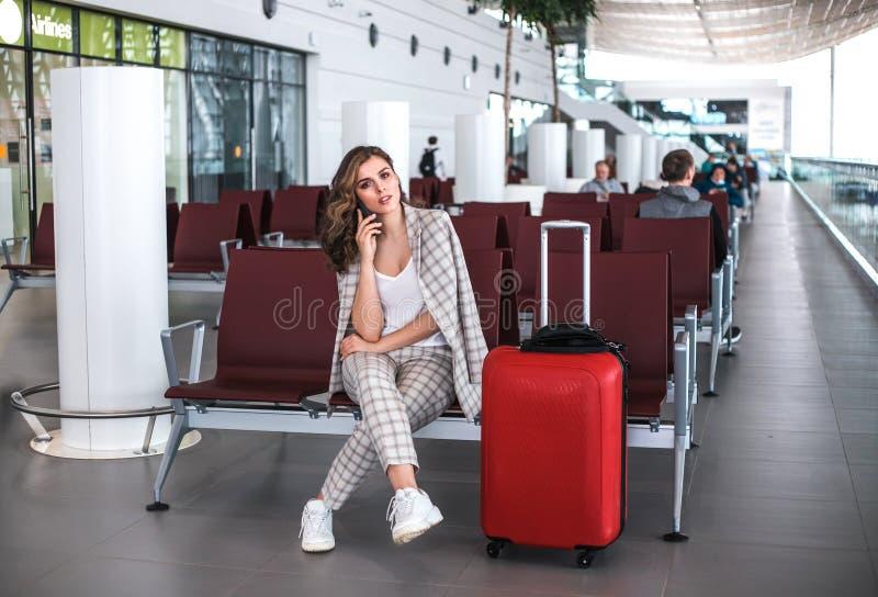 Giovane bella donna che legge i messaggi di telefono nella sala di attesa dell'aeroporto immagine stock libera da diritti