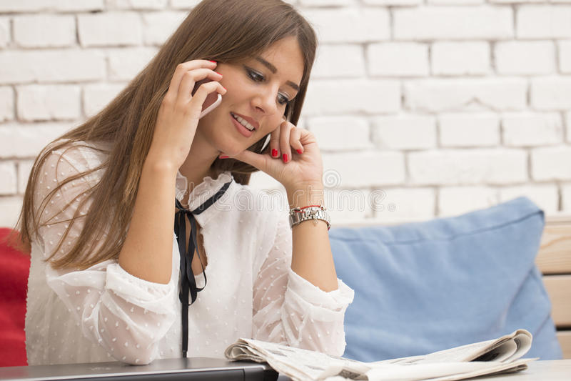 Giovane bella donna che legge il giornale e che parla su una calca immagine stock libera da diritti