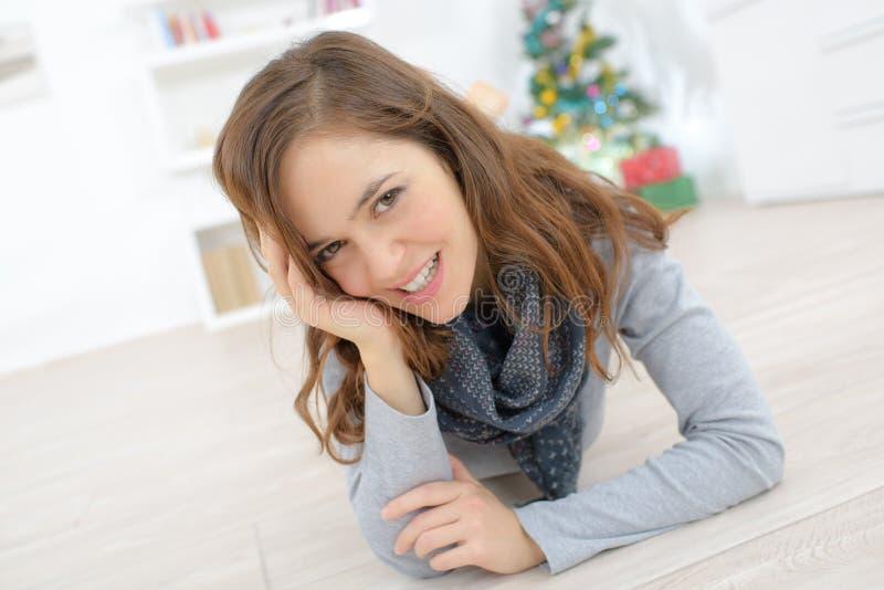 Giovane bella donna che mette su pavimento immagine stock