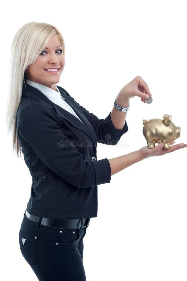 Giovane bella donna che mette una moneta in un grande porcellino salvadanaio fotografia stock
