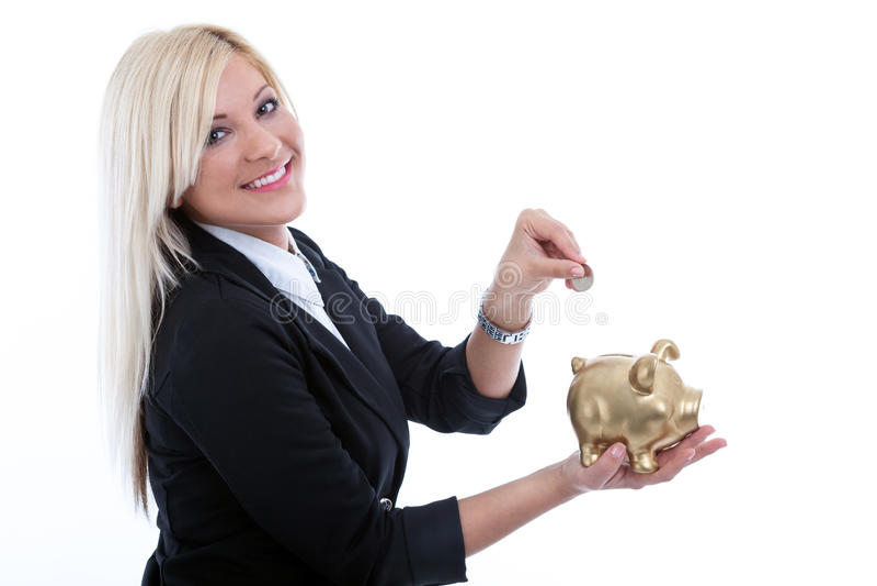 Giovane bella donna che mette una moneta in un grande porcellino salvadanaio fotografia stock libera da diritti