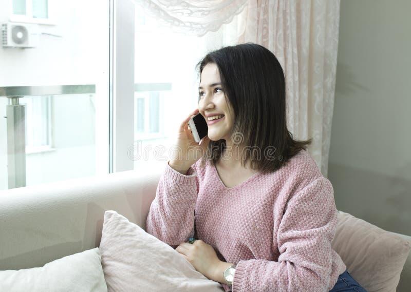 Giovane bella donna che parla dal telefono cellulare sullo strato immagine stock libera da diritti
