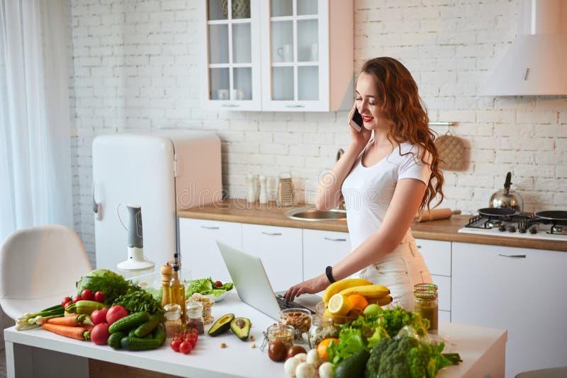 Giovane bella donna che parla sullo smartphone e che utilizza un taccuino mentre cucinando nella cucina moderna Alimento sano ed  fotografia stock libera da diritti