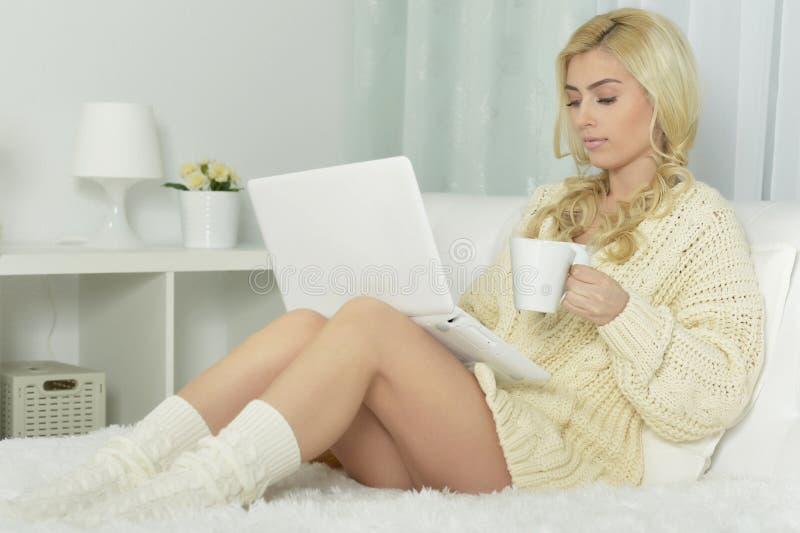 Giovane bella donna che per mezzo di un computer portatile immagine stock libera da diritti