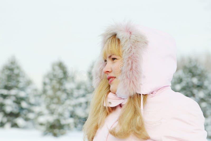 Giovane bella donna che porta rivestimento rosa con una natura piena d'ammirazione del cappuccio nell'inverno immagine stock libera da diritti