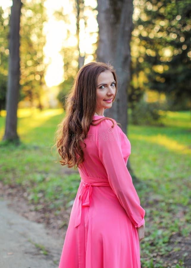 Giovane bella donna che porta vestito rosa che guarda indietro sopra la sua s immagini stock libere da diritti