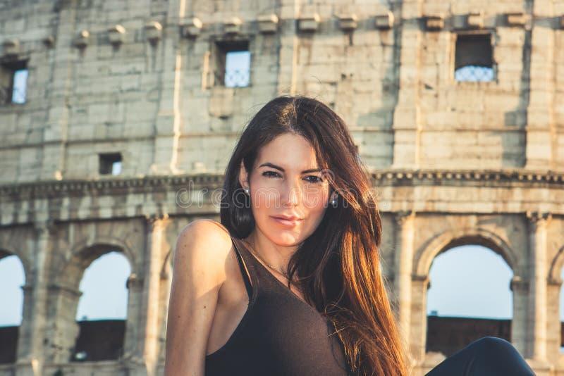 Giovane bella donna che posa davanti al Colosseum Rovine di marmo di arché sopra un cielo blu, Roma, Italia immagine stock
