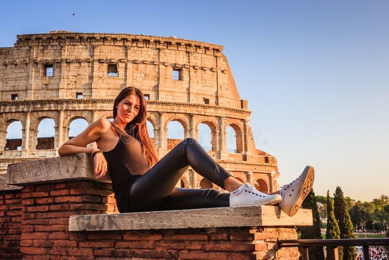 Giovane bella donna che posa davanti al Colosseum Rovine di marmo di arché sopra un cielo blu, Roma, Italia immagini stock libere da diritti