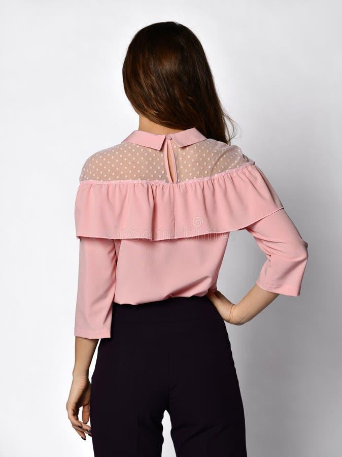Giovane bella donna che posa nella retrovisione della nuova della blusa parte rosa-chiaro casuale del maglione fotografie stock libere da diritti