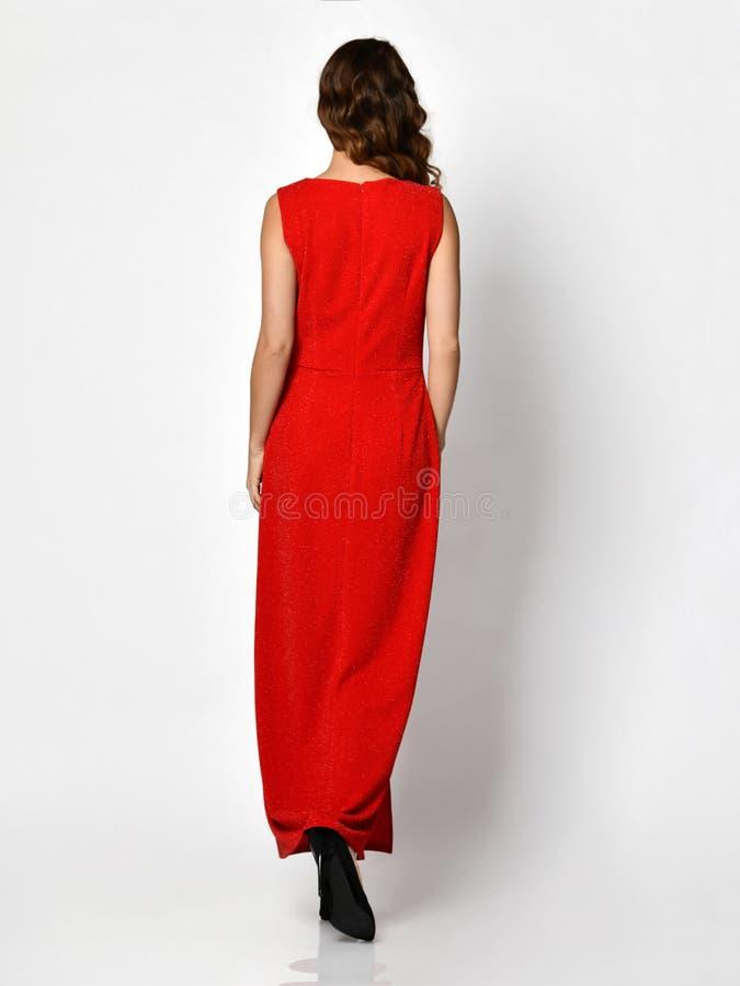 Giovane bella donna che posa nella retrovisione della nuova di modo da inverno del vestito parte piena rossa del corpo fotografia stock