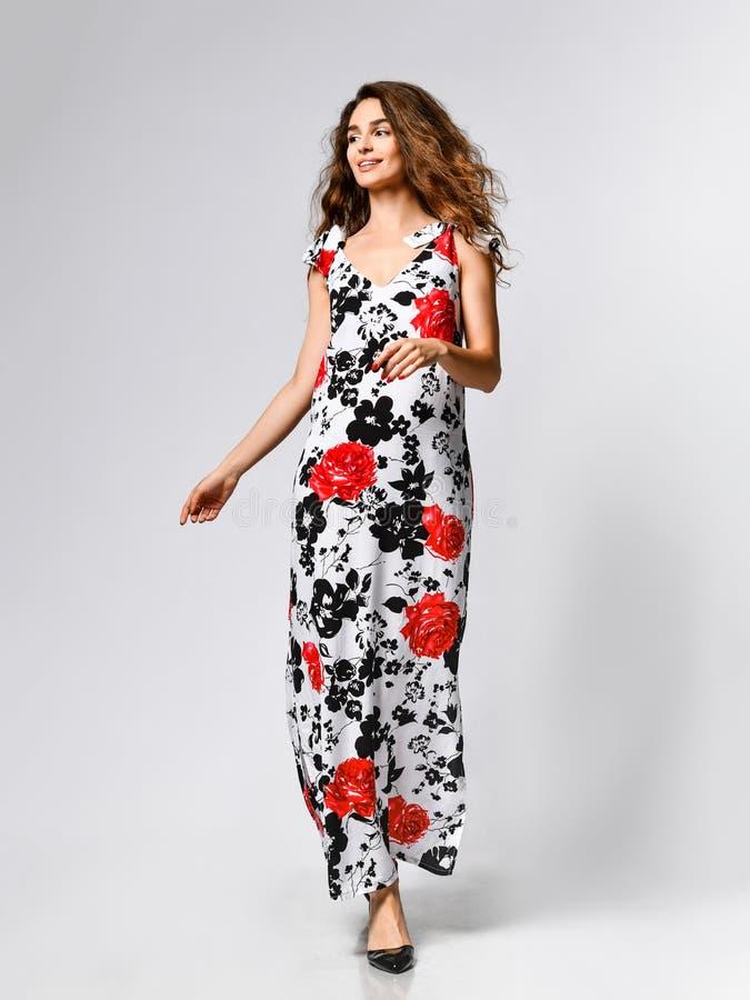 Giovane bella donna che posa in nuovo vestito rosso da modo del modello di fiore su fondo bianco Foto di estate della molla di mo fotografia stock libera da diritti