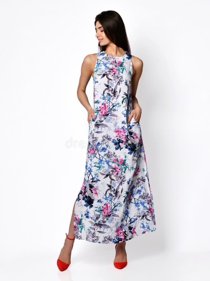 Giovane bella donna che posa in vestito blu da modo dei fiori di nuova estate sull'ente completo delle alte colline su un bianco immagini stock libere da diritti