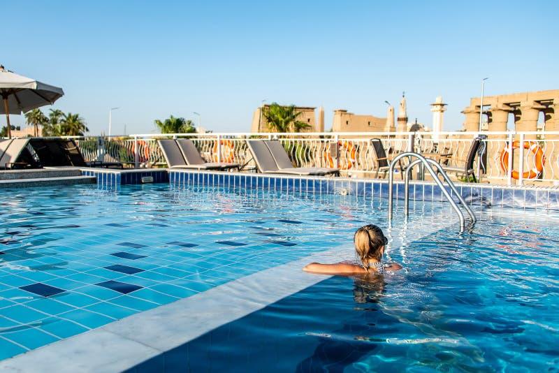 Giovane bella donna che prende il sole nella piscina al parasole considerante lussuoso del parasole nell'Egitto Luxor fotografia stock libera da diritti