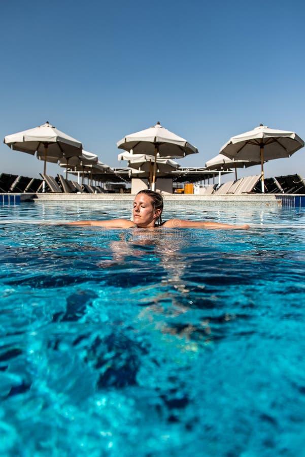 Giovane bella donna che prende il sole nella piscina al parasole considerante lussuoso del parasole nell'Egitto Luxor immagine stock