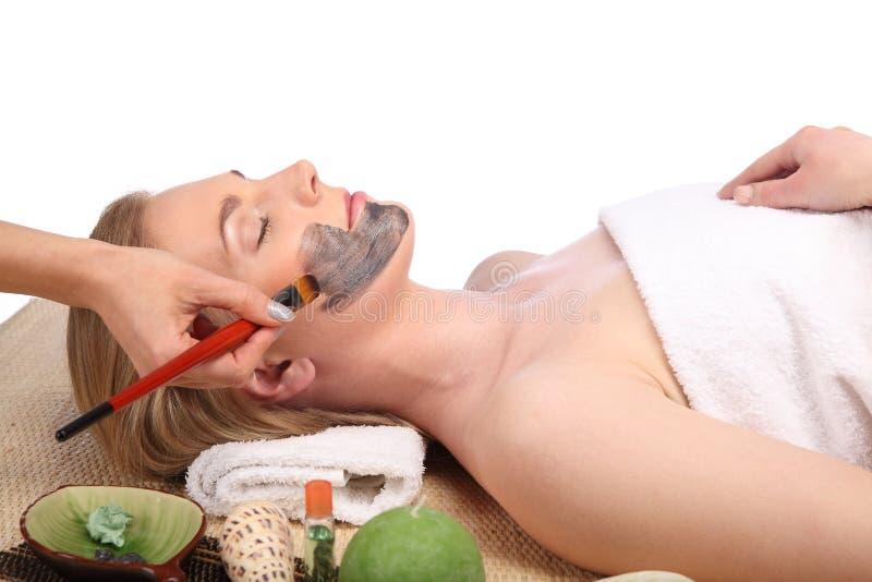 Giovane bella donna che riceve trattamento facciale della stazione termale e di massaggio immagini stock libere da diritti