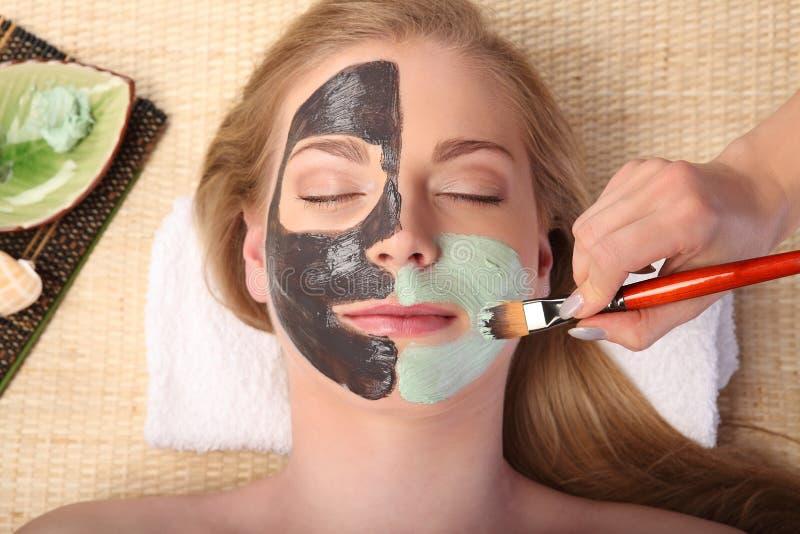 Giovane bella donna che riceve trattamento facciale della stazione termale e di massaggio fotografie stock