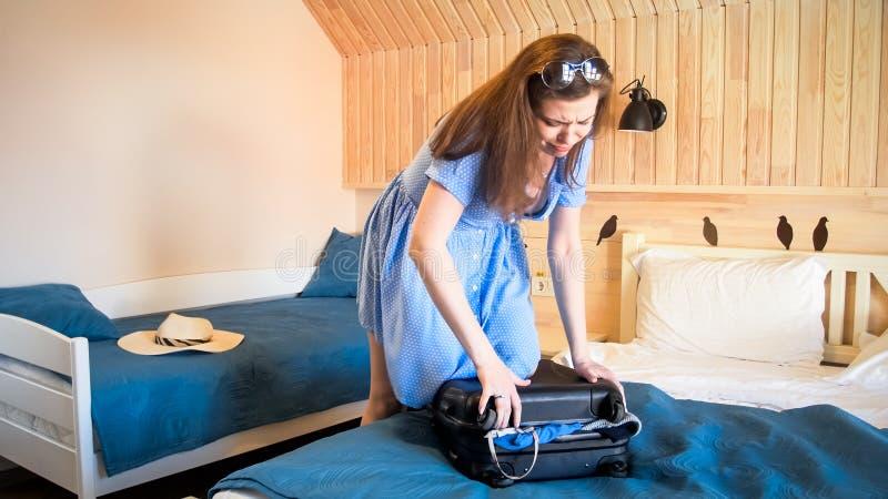 Giovane bella donna che salta sulla valigia che prova a chiuderla fotografie stock