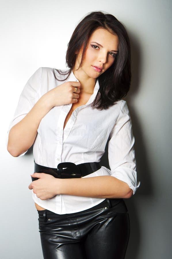 Giovane bella donna che si leva in piedi contro una parete immagini stock libere da diritti