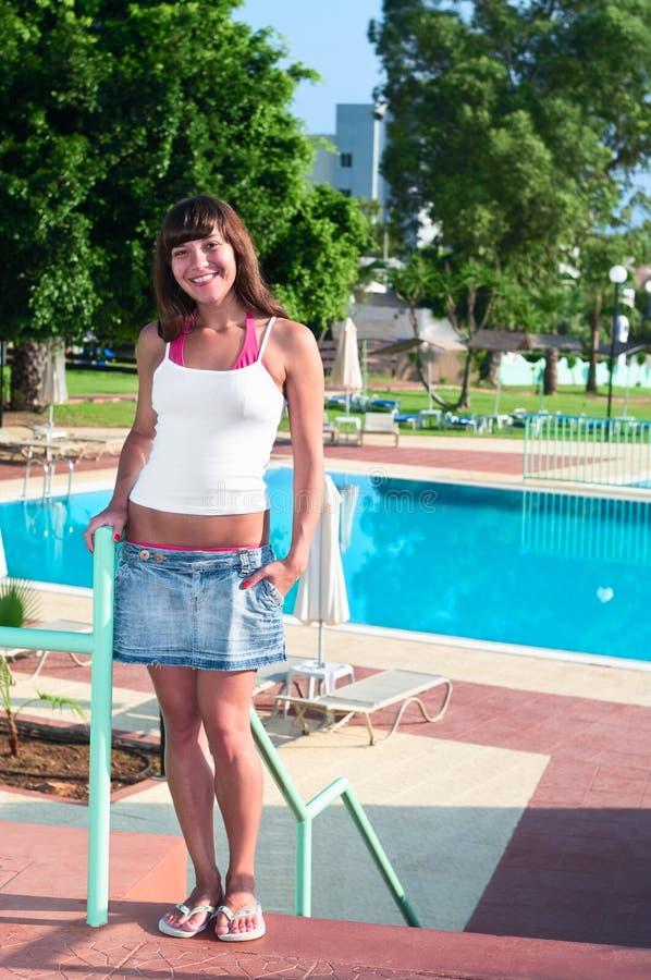 Giovane bella donna che si leva in piedi piscina vicina fotografie stock libere da diritti