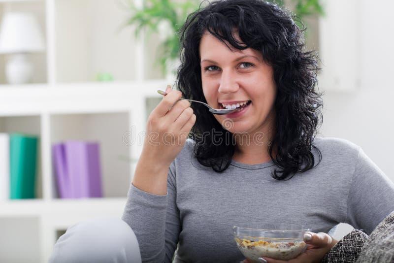 Giovane bella donna che si rilassa a casa, mangiando i cereali fotografia stock