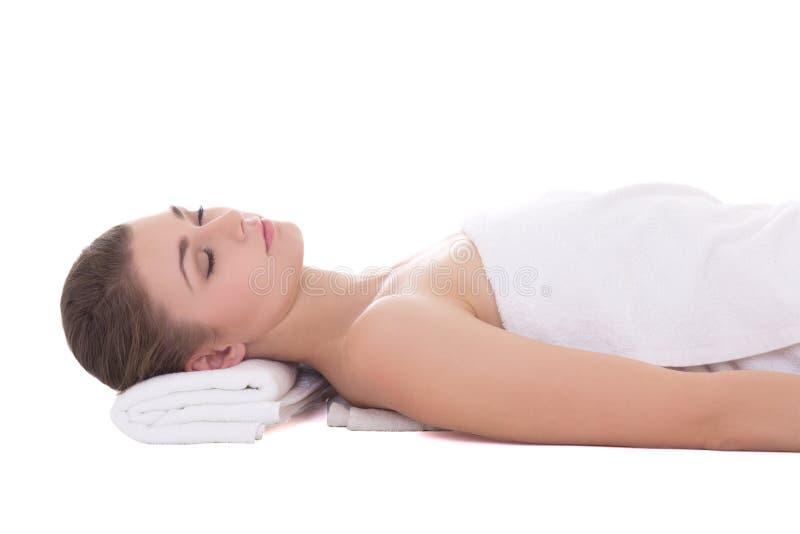 Giovane bella donna che si rilassa su una tavola di massaggio isolata su wh immagine stock